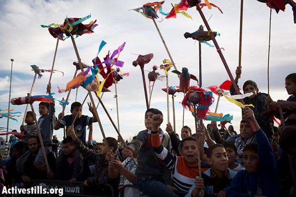 """Children flying kites to the demonstration against the Prawer Plan during November 30 """"Day of Rage"""" protest outside Hura in the Negev Desert."""