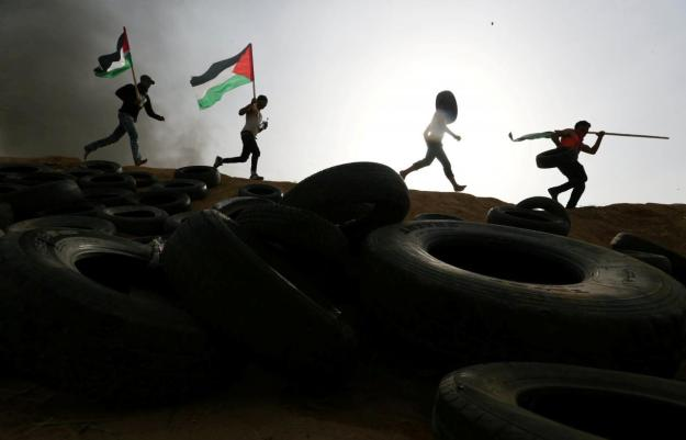 Palestinian protesters run during clashes with Israeli troops at Israel-Gaza border, in the southern Gaza Strip
